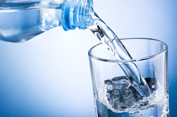 Close-up pouring water from bottle into glass on blue background